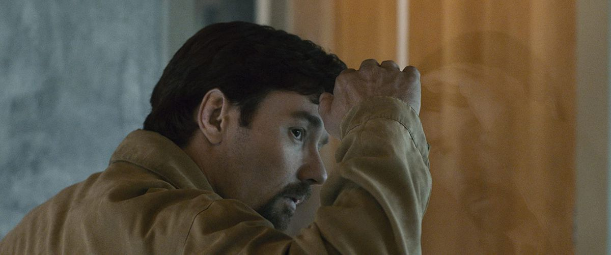Gordo (Joel Edgerton) looks through a window in a still from The Gift