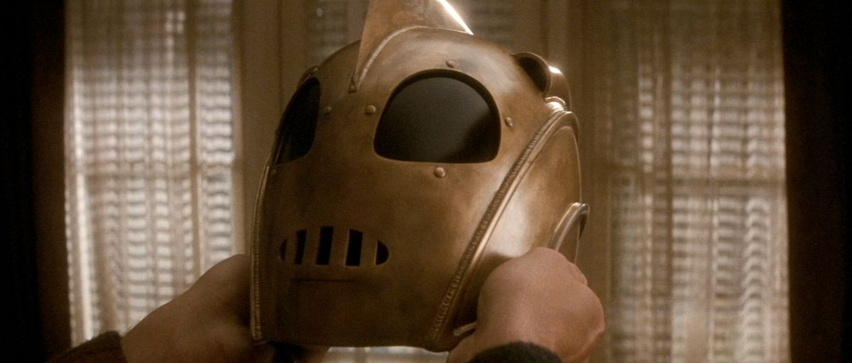 the rocketeer holds his helmet for a close-up