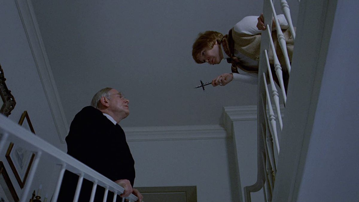 Ellen Burstyn brandishes a crucifix at  Rudolf Schündler in a screenshot from The Exorcist