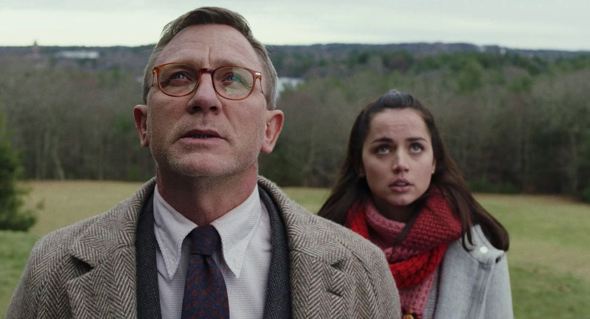 a white man in a suit and wool overcoat (Daniel Craig) and a young Hispanic woman with a red scarf (Ana de Armas) standing outside in a field, looking upward, in Knives Out